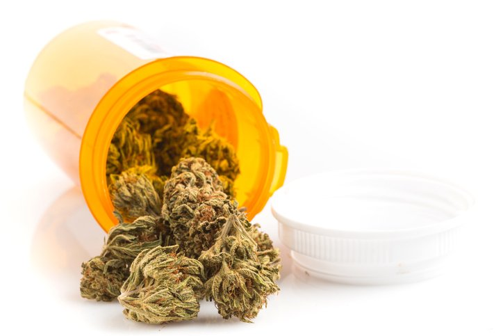 Marijuana buds coming out of a prescription medicine container on white background